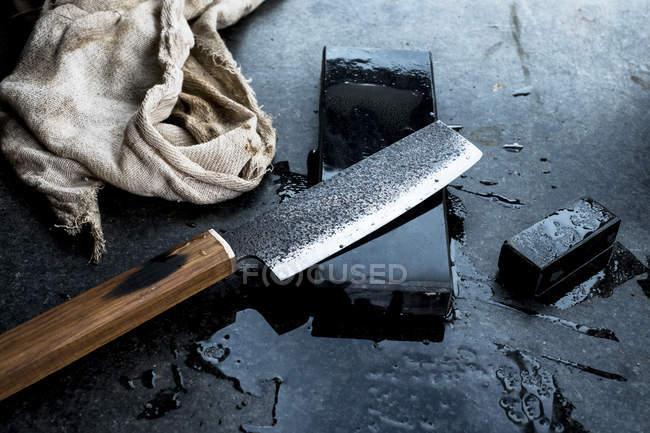 Primo piano ad alto angolo di coltello fatto a mano su pietra per affilare . — Foto stock