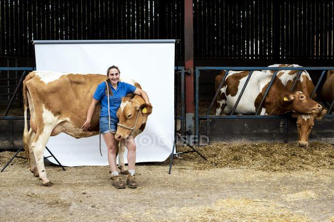 Retrato de agricultora em pé em frente a um celeiro com uma vaca de Guernsey . — Fotografia de Stock