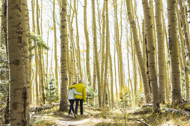 Rear view of mother and teenage daughter hiking in autumn aspens — Stock Photo