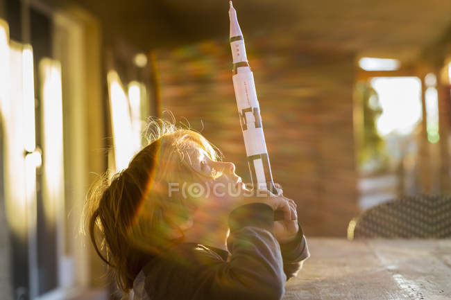 Elementary age boy playing with toy rocket, daydreaming about space flight. — Stock Photo