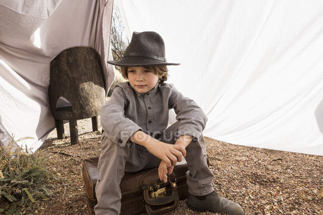 Elementary age boy wearing hat sitting on suitcase in outdoor tent made of sheets — Stock Photo