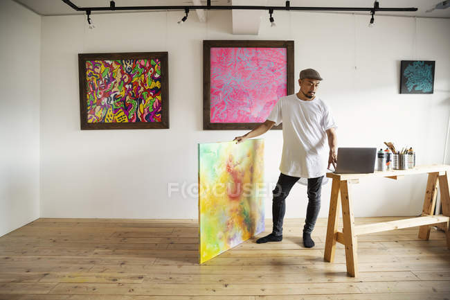 Japanese man standing in art gallery, holding abstract artwork, looking at laptop computer. — Stock Photo