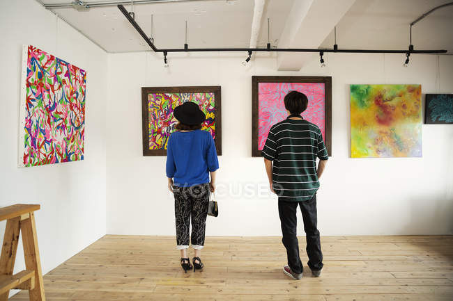 Rear view of man and woman looking at abstract paintings in an art gallery. — Stock Photo