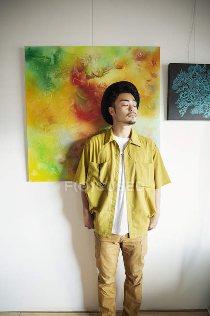 Japanese man in hat standing in front of abstract paintings in an art gallery. — Stock Photo