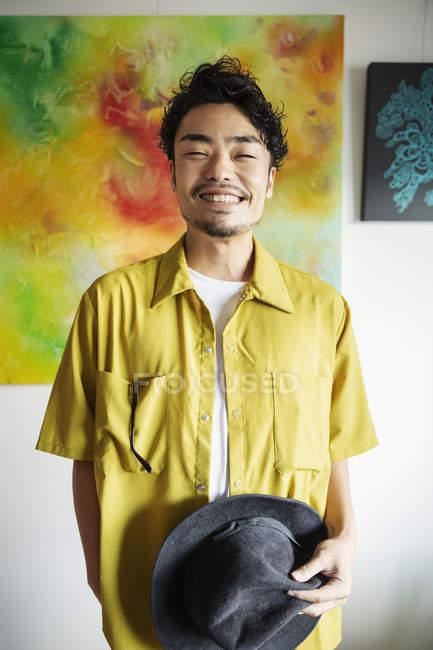 Японский мужчина, стоящий перед абстрактными картинами в художественной галерее, улыбающийся в камеру . — стоковое фото