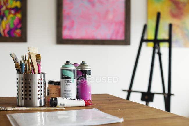 Interior view of art gallery with studio space, easel and cans of spray paint on a table. — Stock Photo