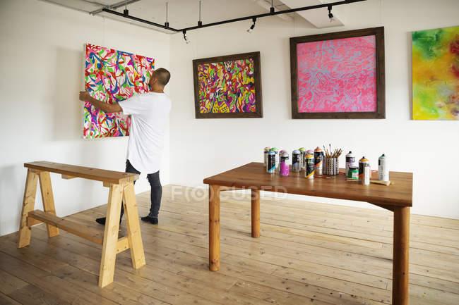 Человек, стоящий в художественной галерее, вешающий красочную картину на белую стену . — стоковое фото