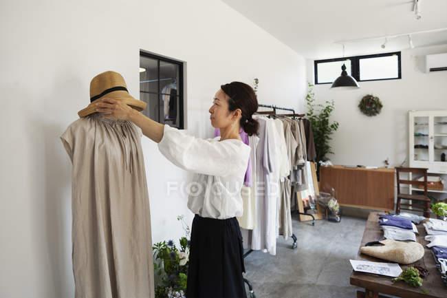 Femme japonaise debout dans une petite boutique de mode, arrangeant chapeau sur mannequin . — Photo de stock