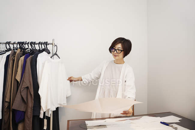 Mulher japonesa em óculos trabalhando em uma mesa em uma pequena boutique de moda . — Fotografia de Stock