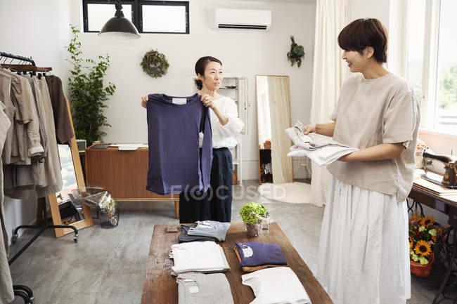 Due donne giapponesi in piedi in una piccola boutique di moda, organizzare t-shirt su un tavolino . — Foto stock