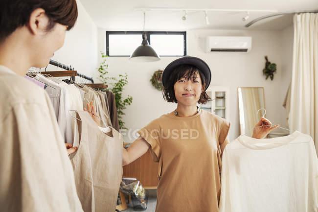 Дві японки стоять у маленькому бутіку, дивлячись на верхівки.. — стокове фото