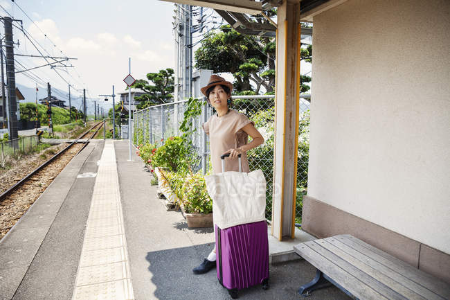 Japanese woman wearing hat standing on railway station platform with shopping bag and pink suitcase. — Stock Photo