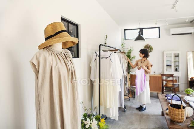Donna giapponese in piedi in una boutique, guardando i vestiti su una rotaia . — Foto stock