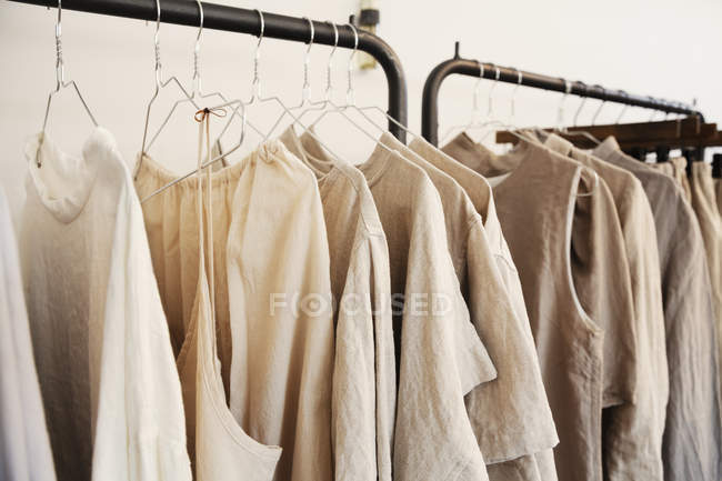 Close-up of selection of clothes in natural colors on a rail in a boutique. — Stock Photo