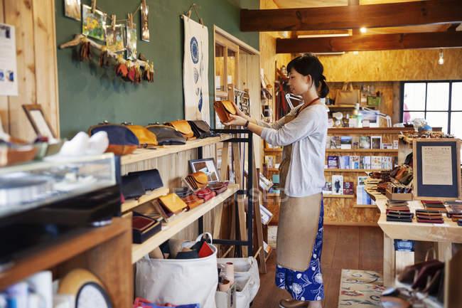 Femme japonaise portant un tablier debout dans une boutique en cuir, tenant un sac d'embrayage en cuir . — Photo de stock