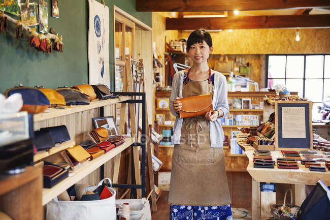 Japanese woman wearing apron standing in a leather shop, holding leather clutch bag, smiling in camera. — стокове фото