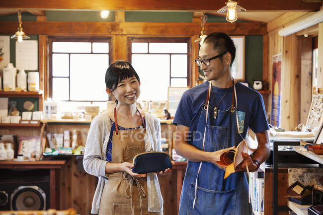 Smiling Japanese woman and man wearing aprons and glasses standing in a leather shop. — Stock Photo