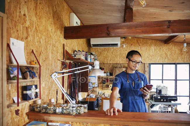 Japanese man wearing blue apron and glasses standing in a leather shop, using mobile phone. — Stock Photo