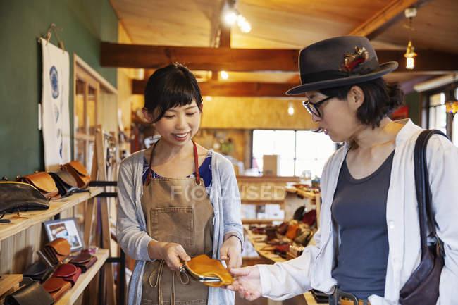 Две японки, стоящие в кожаном магазине с кожаной сумкой . — стоковое фото