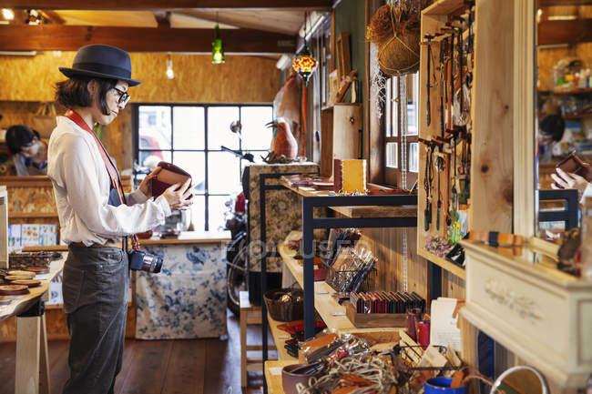 Femme japonaise portant chapeau et lunettes naviguant marchandises dans une boutique de cuir . — Photo de stock