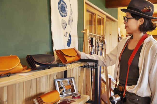 Mulher japonesa usando chapéu e óculos navegando mercadoria em uma loja de couro . — Fotografia de Stock