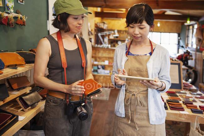Deux femmes japonaises debout dans une boutique de cuir, tenant sac à main en cuir et tablette numérique . — Photo de stock