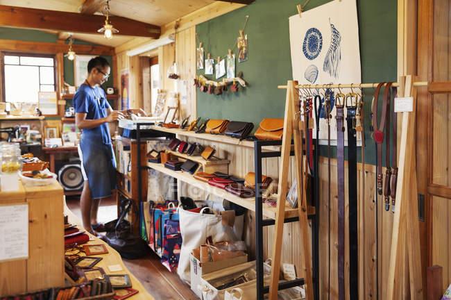 Close-up de artigos de couro e homem japonês em pé em uma loja de couro . — Fotografia de Stock