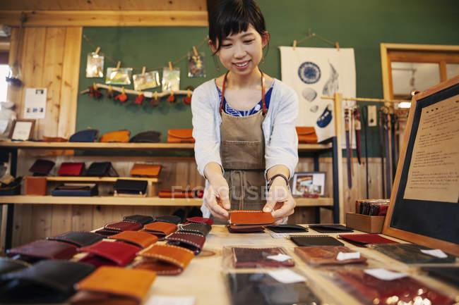Японка, стоящая за столом, работающая в кожаном магазине . — стоковое фото