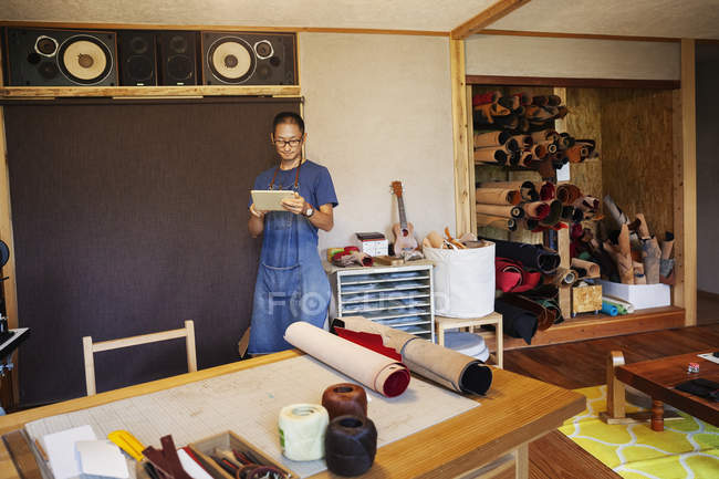 Japanese man wearing blue apron and glasses standing in a leather shop, using digital tablet. — Stock Photo