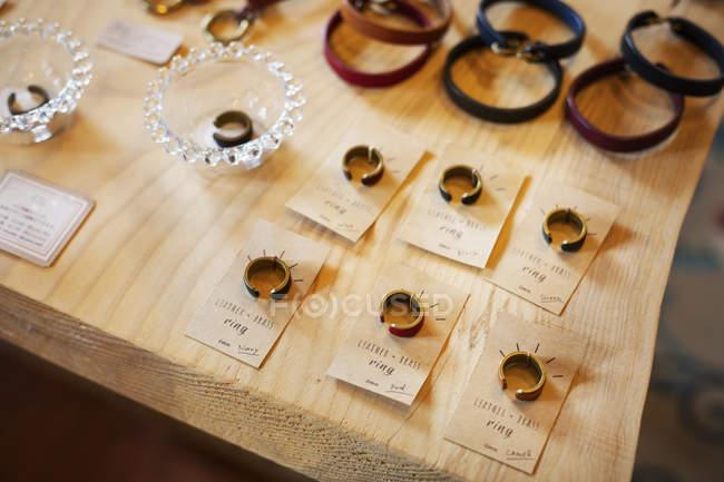Крупный план кольца и кожаные браслеты на столе в кожаном магазине . — стоковое фото