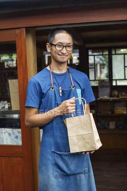 Japonais portant tablier bleu et lunettes debout devant une boutique de cuir, tenant un sac à provisions, souriant à la caméra . — Photo de stock