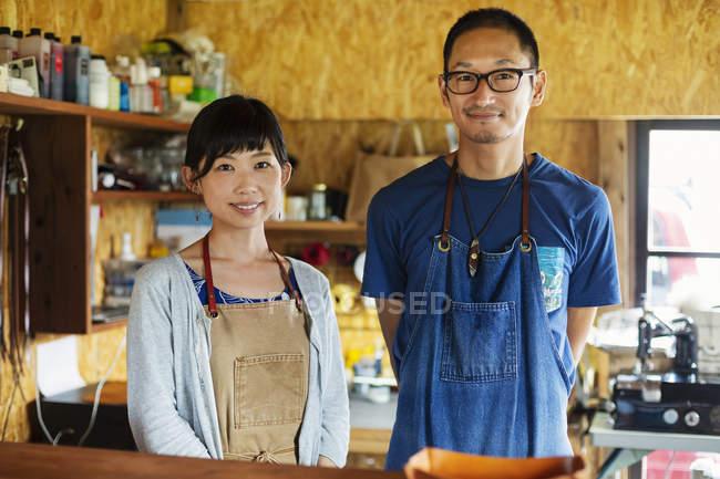 Японська жінка і чоловік у синьому фартусі стоять у шкіряній крамниці, посміхаючись у фотоапараті.. — стокове фото