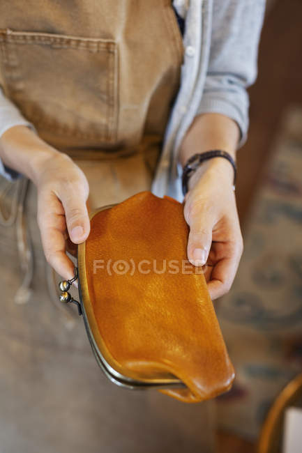 High angle close-up of person holding an leather purse in artisan store. — Stock Photo