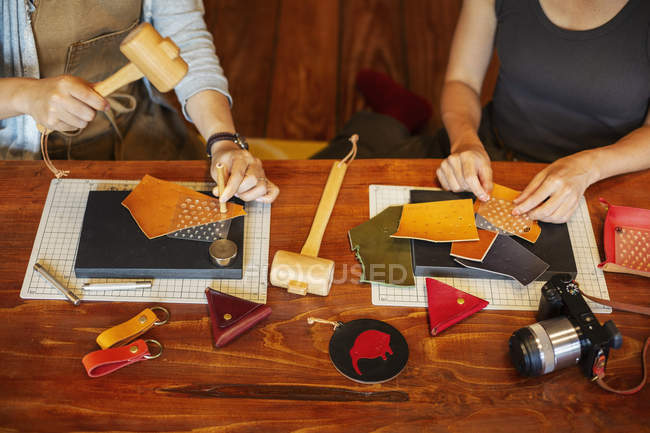 High angle view of two women sitting at a table, working in a leather shop. — Stock Photo