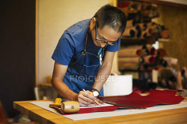 Japanese man wearing blue apron working in a leather shop. — Stock Photo