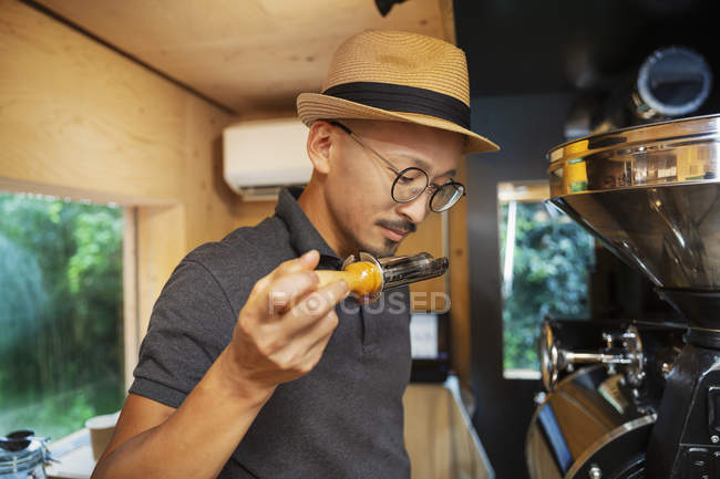 Japanese man wearing hat and glasses standing in an Eco Cafe, smelling freshly roasted coffee beans. — Stock Photo