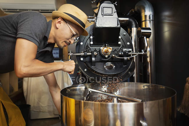 Japanese man wearing hat and glasses standing in an Eco Cafe, operating coffee roaster machine. — Stock Photo