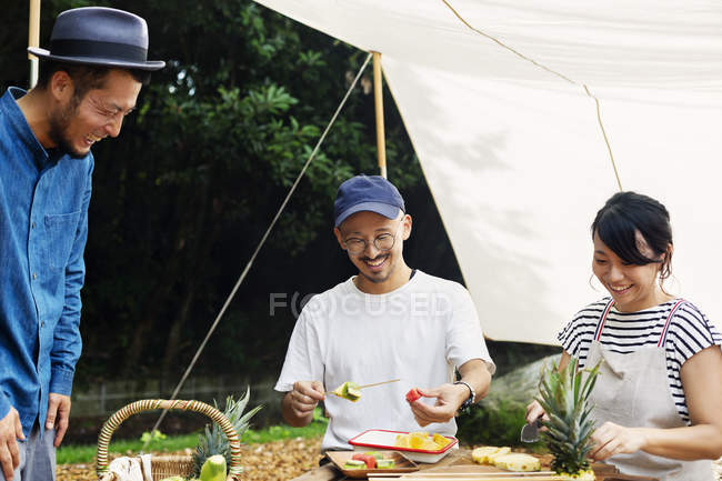 Japanese men and woman gathered around a table under a canopy, preparing fresh fruits. — Stock Photo
