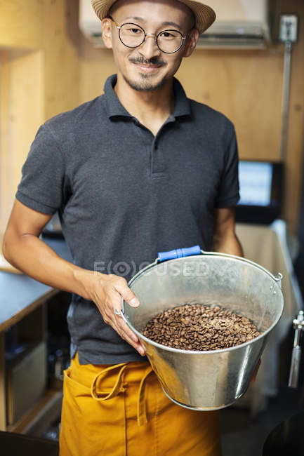 Japanese man standing in Eco Cafe, holding metal bucket with freshly roasted coffee beans, smiling in camera. — Stock Photo
