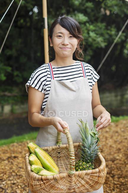 Femme japonaise souriante portant un tablier debout à l'extérieur, tenant le panier avec des fruits et légumes frais, regardant à la caméra . — Photo de stock