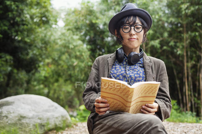 Japanese woman wearing glasses and hat sitting on chair outside Eco Cafe, reading book. — Stock Photo