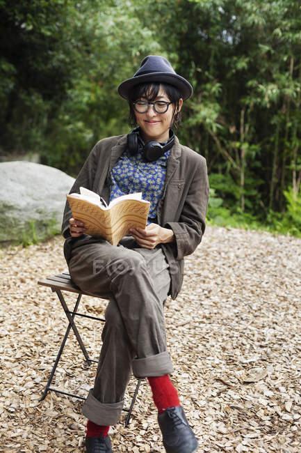 Японская женщина в очках и шляпе сидит на стуле возле Эко Кафе, читает книгу . — стоковое фото