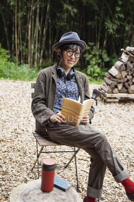 Femme japonaise portant des lunettes et un chapeau assis sur une chaise à l'extérieur Eco Cafe, livre de lecture . — Photo de stock
