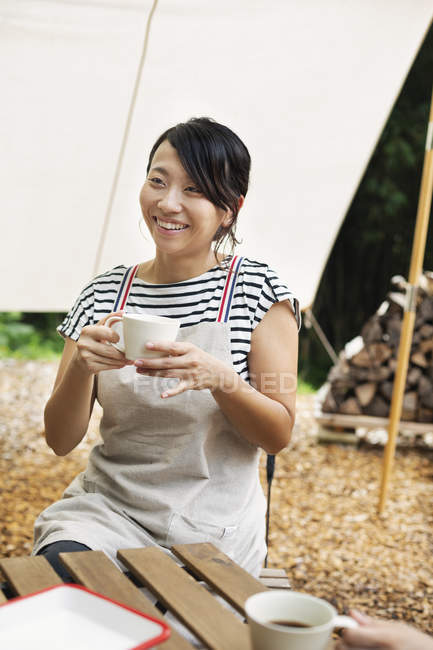 Smiling Japanese woman sitting outdoors at a table, drinking cup of coffee. — Stock Photo