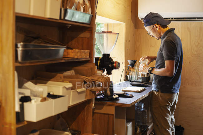 Japanese man wearing baseball cap and glasses standing in an Eco Cafe, preparing cup of coffee. — Stock Photo