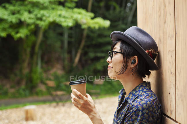 Japanese woman wearing glasses and hat standing outside Eco Cafe, holding paper cup, side view. — Stock Photo