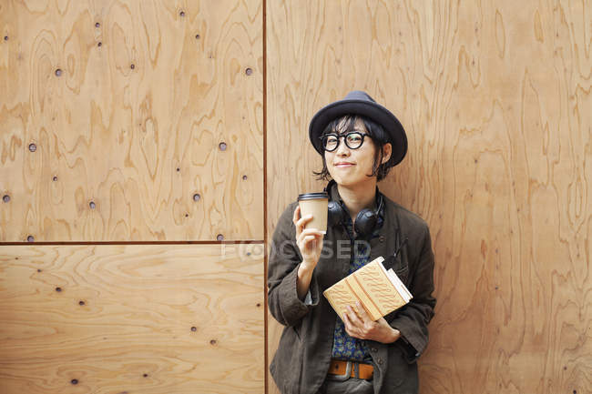 Japanese woman wearing glasses and hat standing outside Eco Cafe, holding paper cup and notebook. — Stock Photo