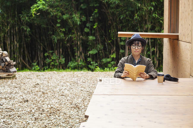Japanese woman wearing glasses and hat sitting at a table outside Eco Cafe, reading book. — Stock Photo