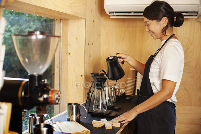 Japanese woman wearing apron standing in an Eco Cafe, preparing coffee. — Stock Photo