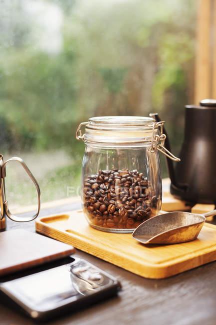 Gros plan de cafetière, bocal en verre avec grains de café et pelle à café en métal sur planche en bois . — Photo de stock